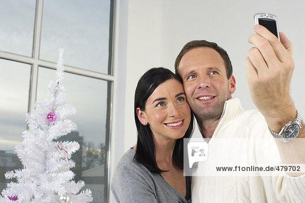 Paar fotografiert sich mit einem Handy vor einem weißen Weihnachtsbaum  fully_released