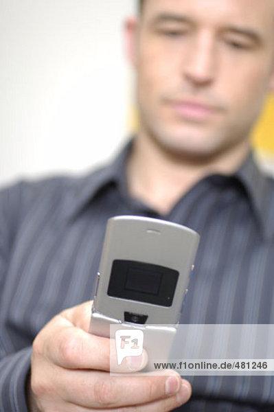 junger Mann sein Handy für Text-Nachrichten überprüfen
