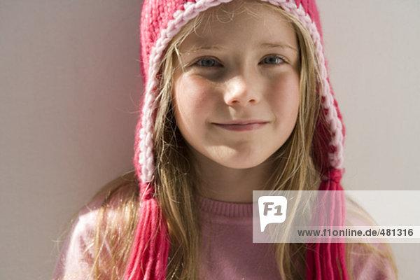 girl wearing pink hat looking at camera