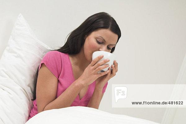 Portrait einer jungen Frau aus weißen Tasse trinken