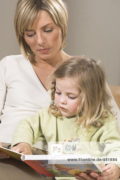 Porträt von Mutter Lesung Bilderbuch zusammen mit ihrer kleinen Tochter