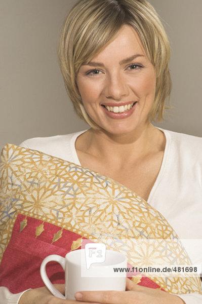 Portrait of lächelnd junge Frau hält Kissen und Tee cup