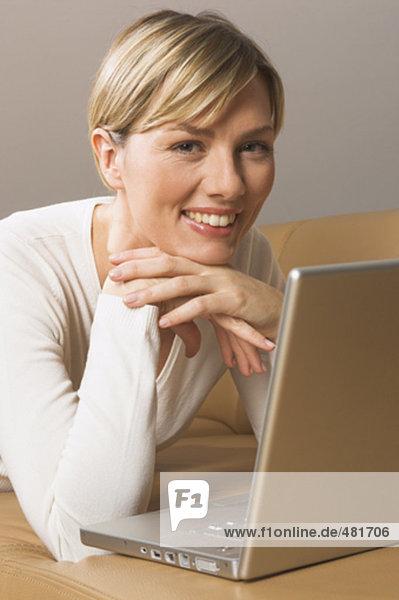 Portrait blonde Frau auf Sofa mit Notebook-computer