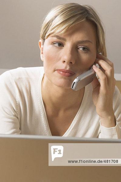 Portrait einer jungen Frau mit Notebook-Computer sprechen auf Handy