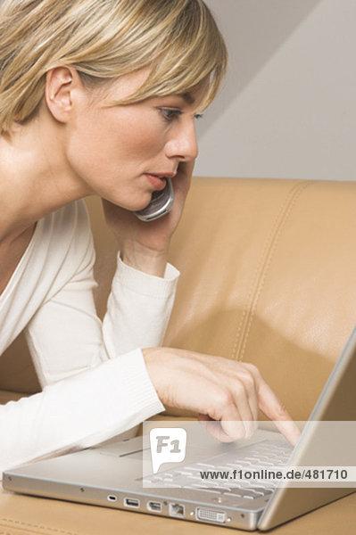 Portrait einer jungen Frau liegend auf Sofa eingeben auf Notebook-Computer und Handy hören
