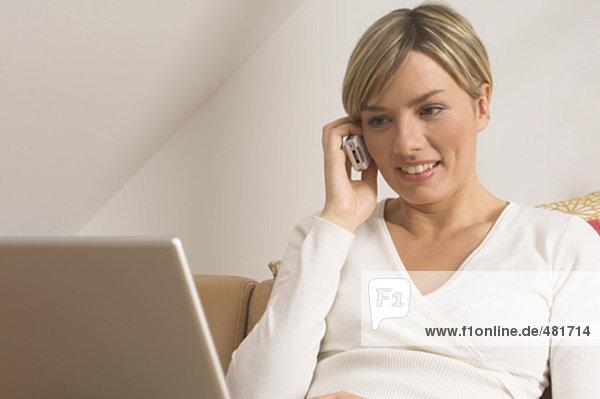 Portrait einer jungen Frau mit Handy und Notebook-computer