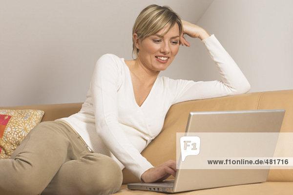 Porträt von lächelnde junge Frau auf Couch sitzen und arbeiten mit Notebook-computer