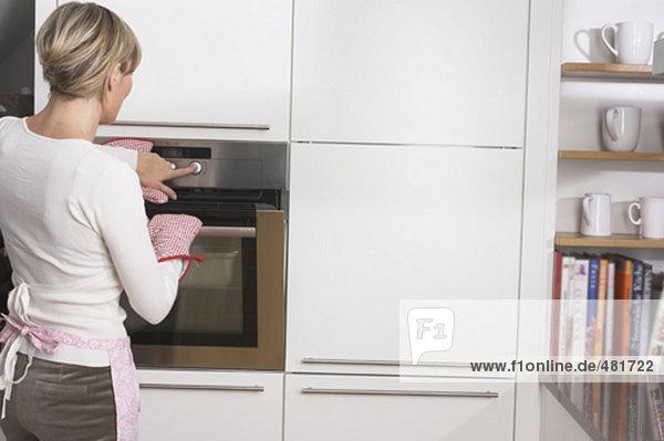 Rückansicht des blonde Hausfrau am Ofen