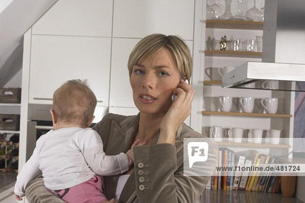 betonte junge geschäftsfrau in Küche hält Baby stehen und Reden auf Handy