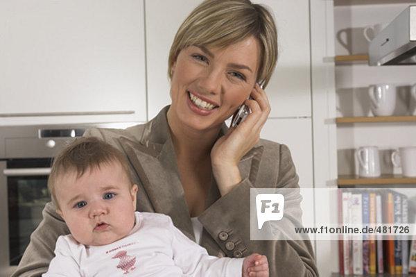 Porträt von lächelnden jungen geschäftsfrau in Küche hält Baby und sprechen auf Handy