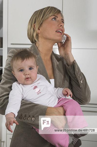 Porträt der jungen geschäftsfrau hält Baby beim sprechen auf Handy