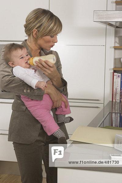 junge geschäftsfrau Fütterung ihr Baby beim Lesen der Dokumente