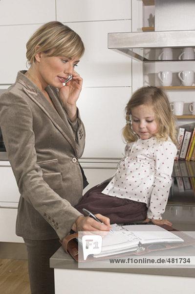 junge geschäftsfrau in Küche betrachten ihre Tochter beim Anhören Handy