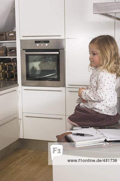 Sad little mädchen sitzen allein in Küche