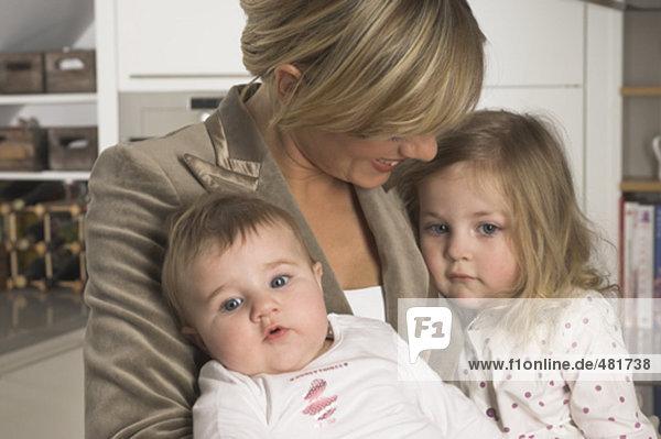 Porträt der jungen geschäftsfrau Kuscheln ihren kleinen Töchtern