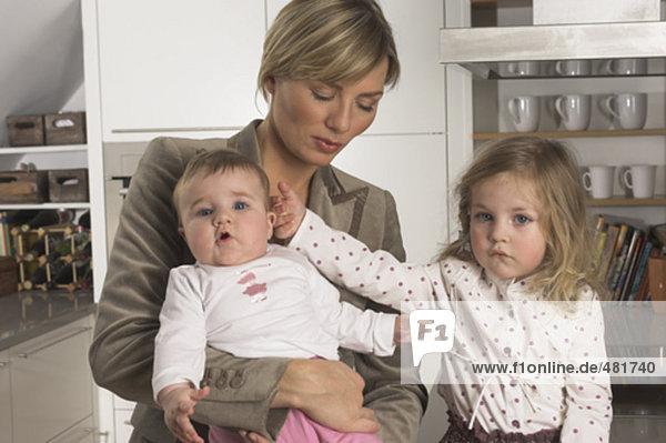kleines Mädchen ihre jüngere Schwester berühren Besitz ihrer Mutter