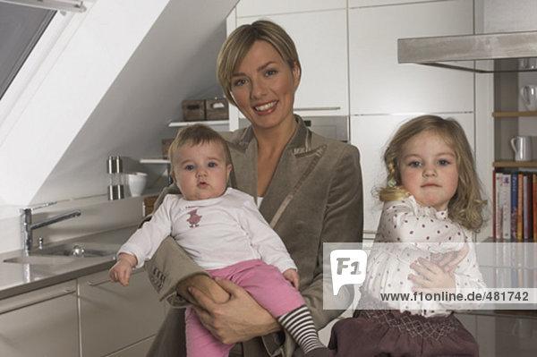 Porträt der jungen geschäftsfrau in Küche mit ihren beiden kleinen Töchtern