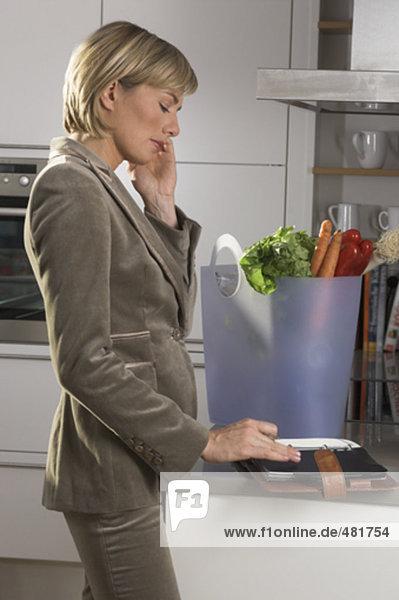 Porträt der jungen geschäftsfrau in Küche stehen  sprechen auf Handy und Blick auf ihr Tagebuch