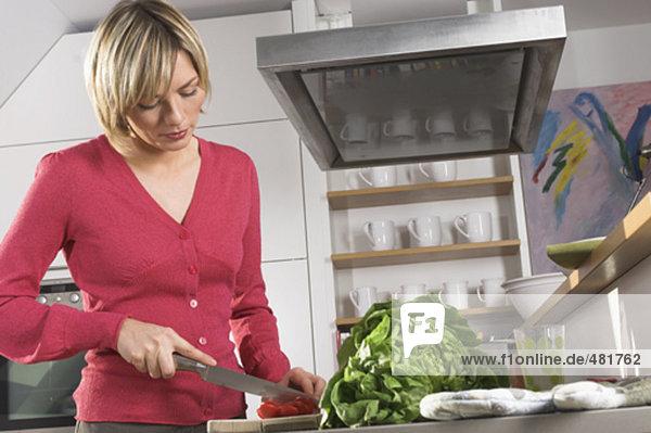 Portrait einer jungen Frau Vorbereitung Mahlzeit in Küche  schneiden Paprika