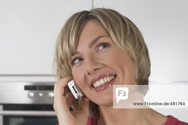 Headshot lächelnd jungen Frau mit Handy in Küche