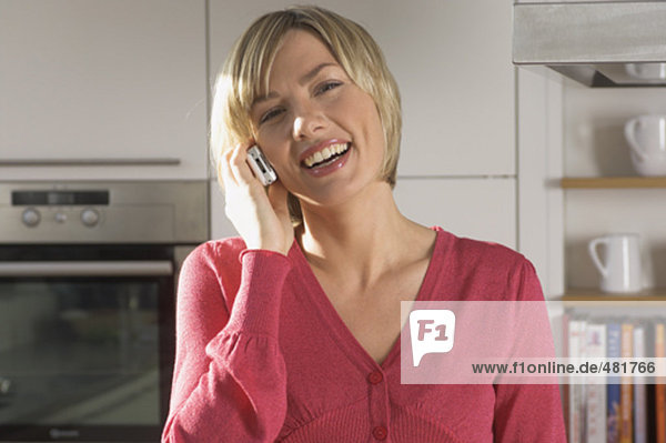 portrait of smiling young woman with cellphone in kitchen