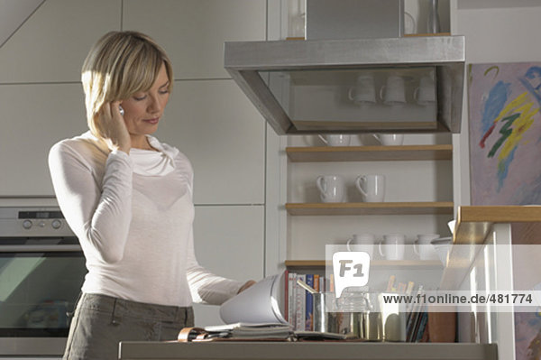 low angle view of young woman talking on cellphone in kitchen and looking at her diary