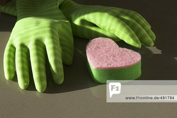 Stillleben mit Gummi-Handschuhe und Schwamm in Form von Herzen