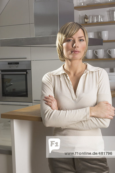 portrait of blonde young woman standing in kitchen