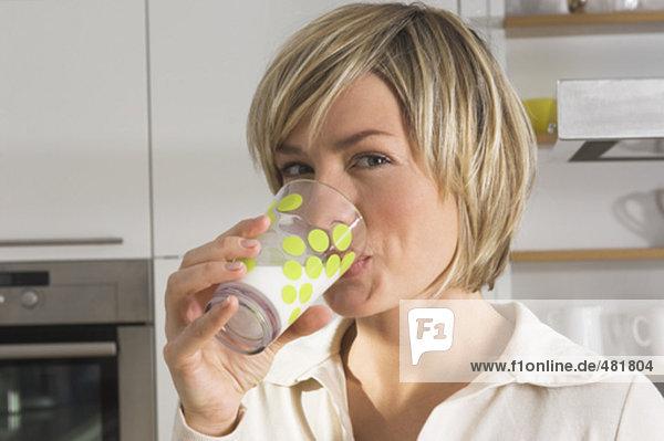 Headshot jungen Frau Glas Milch zu trinken in Küche