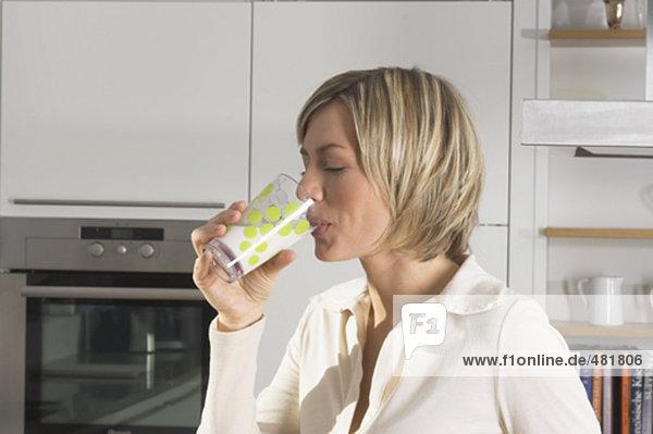 Portrait einer jungen Frau trinken Glas Milch in Küche