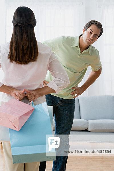 Frau versteckt Einkaufstaschen vor ihrem Mann