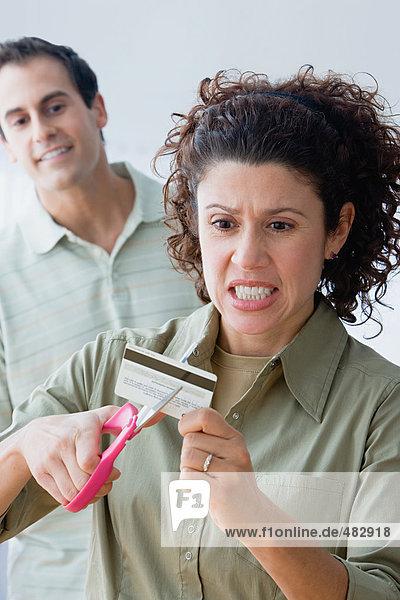 Ein Paar schneidet eine Kreditkarte auf.