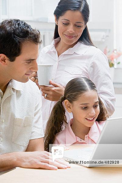 Familie,  die einen Laptop benutzt