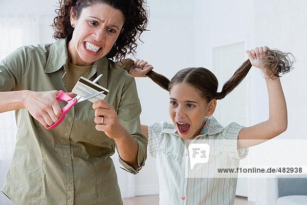 Mutter zerschneidet eine Kreditkarte