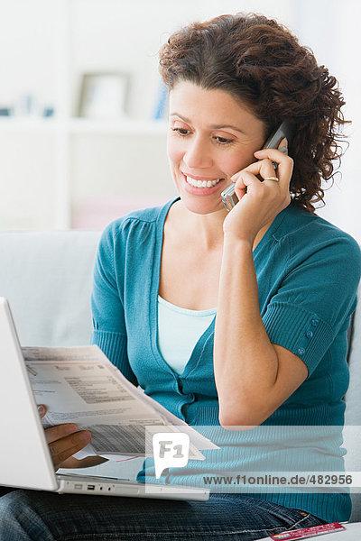 Frau bezahlt Rechnungen am Telefon