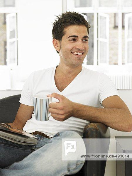 Ein Mann mit einer Tasse und eine Zeitung in einem Sessel.