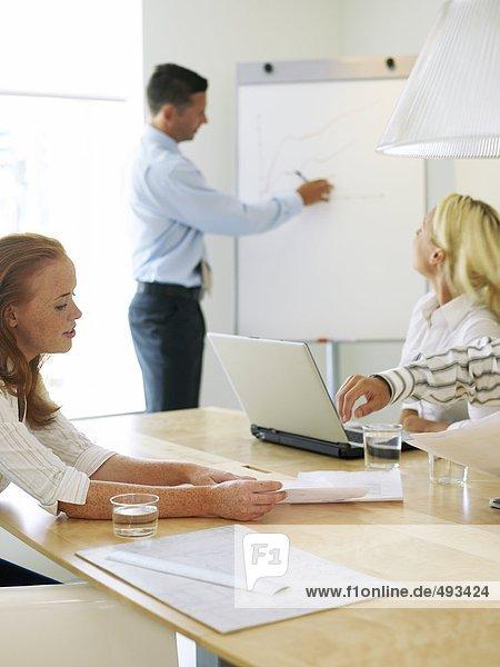Zwei Frauen und ein Mann mit einem Treffen.