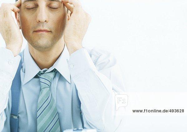 Mann reibt Schläfen mit geschlossenen Augen
