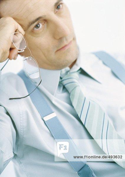 Mann hält eine Brille  lehnt sich an die Hand  denkt nach