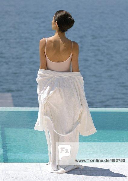 Woman standing overlooking water  bathrobe off shoulders