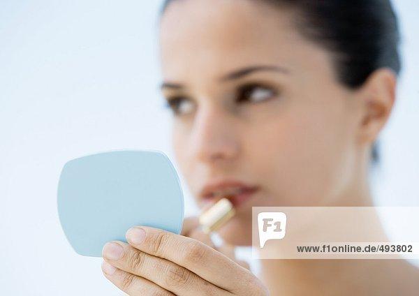 Frau setzt Lippenstift auf  Fokus auf Hand hält Spiegel im Vordergrund  Mund