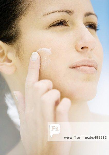 Frau  die Feuchtigkeitscreme auf die Wange aufträgt