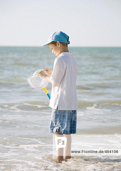 Junge im Meer stehend mit Fischernetz