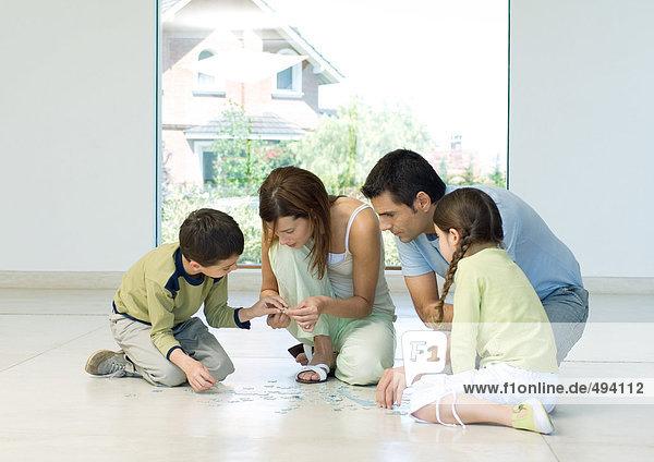 Familie beim Zusammenstellen von Rätseln