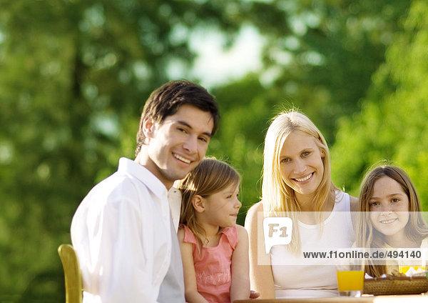 Familie sitzend am Tisch mit Saft  im Freien