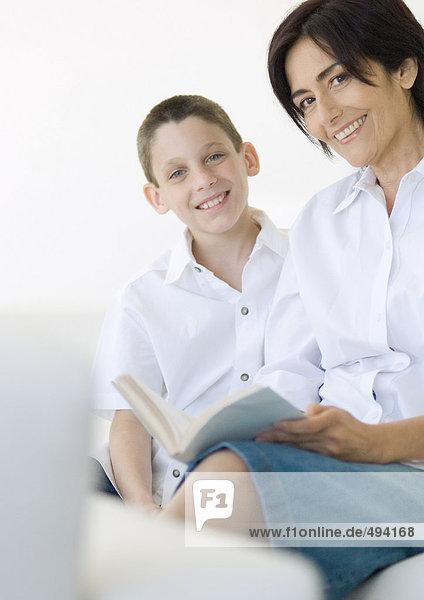 Junge und reife Frau mit Buch  lächelnd vor der Kamera