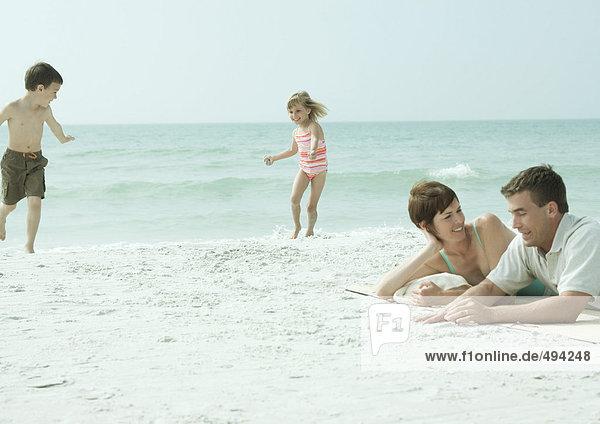 Familie am Strand  Eltern liegen auf Sand  während Kinder spielen