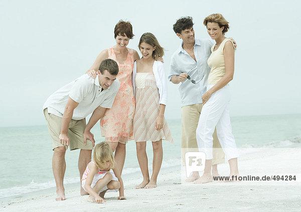 Gruppe steht am Strand  Mann beugt sich vor  um mit der Tochter zu reden.