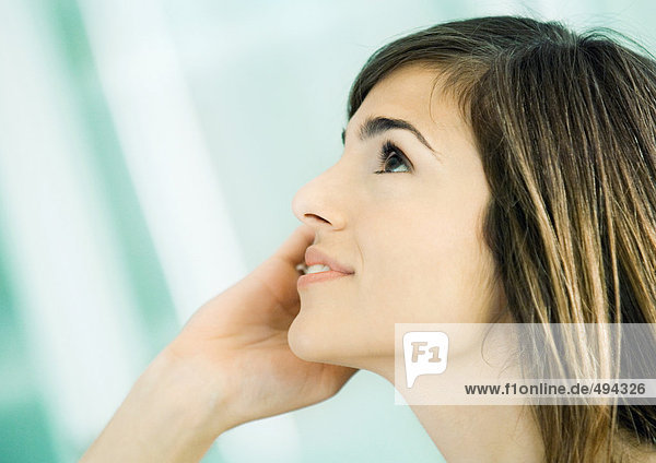 Young woman using cell phone  side view