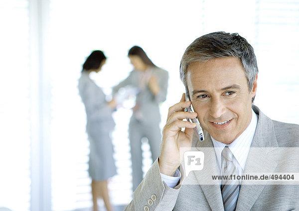 Geschäftsmann mit Handy  Kollegen im Hintergrund